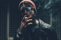Young male hipster smoking cigarette in dark city doorway at night 11015327871| 写真素材・ストックフォト・画像・イラスト素材|アマナイメージズ