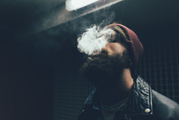 Young male hipster in knit hat smoking at night 11015327872| 写真素材・ストックフォト・画像・イラスト素材|アマナイメージズ