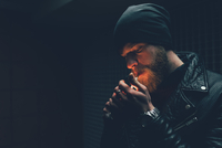 Young male hipster in knit hat igniting cigarette at night 11015327873| 写真素材・ストックフォト・画像・イラスト素材|アマナイメージズ