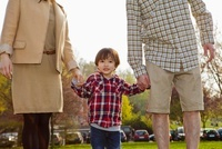 A young boy in between his parents, holding hands 11016023395| 写真素材・ストックフォト・画像・イラスト素材|アマナイメージズ