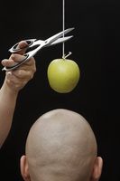A woman cutting an apple on a string above the head of a man 11016024237| 写真素材・ストックフォト・画像・イラスト素材|アマナイメージズ