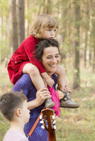 Happy woman carrying daughter while talking to son in forest 11016029631| 写真素材・ストックフォト・画像・イラスト素材|アマナイメージズ