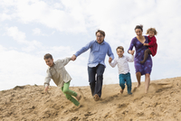 Cheerful family holding hands while running on sand dune against sky 11016029633| 写真素材・ストックフォト・画像・イラスト素材|アマナイメージズ