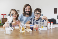 Portrait of father and children doing science experiment at home 11016031639| 写真素材・ストックフォト・画像・イラスト素材|アマナイメージズ