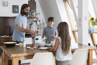 Father and children setting table for lunch in kitchen 11016031649| 写真素材・ストックフォト・画像・イラスト素材|アマナイメージズ
