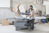 Full length of carpenter using a sliding table saw in workshop 11016031701| 写真素材・ストックフォト・画像・イラスト素材|アマナイメージズ