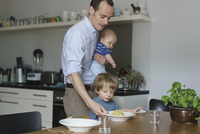 Father carrying toddler while giving food to son at dining table 11016032415| 写真素材・ストックフォト・画像・イラスト素材|アマナイメージズ