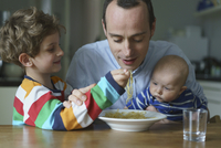 Boy feeding noodles to father carrying son at table 11016032444| 写真素材・ストックフォト・画像・イラスト素材|アマナイメージズ