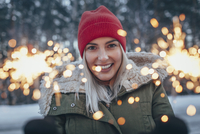 Portrait of smiling woman holding sparklers during winter 11016033216| 写真素材・ストックフォト・画像・イラスト素材|アマナイメージズ