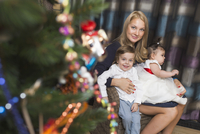 Portrait of mother sitting with son and daughter celebrating Christmas 11016033348| 写真素材・ストックフォト・画像・イラスト素材|アマナイメージズ