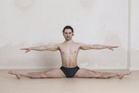 Portrait of confident man with arms outstretched doing splits while performing yoga 11016033448| 写真素材・ストックフォト・画像・イラスト素材|アマナイメージズ