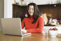 Close-up of mature woman using laptop on table at home 11016033493| 写真素材・ストックフォト・画像・イラスト素材|アマナイメージズ