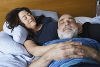 Close-up of mature couple sleeping on bed at home 11016033500| 写真素材・ストックフォト・画像・イラスト素材|アマナイメージズ