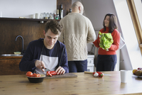 Teenager cutting vegetables on table while helping parents in kitchen 11016033527| 写真素材・ストックフォト・画像・イラスト素材|アマナイメージズ