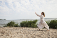 Side view of woman practicing yoga on sea shore against sky 11016033572| 写真素材・ストックフォト・画像・イラスト素材|アマナイメージズ