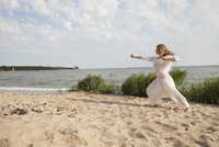 Young woman practicing yoga on sea shore at beach against sky 11016033579| 写真素材・ストックフォト・画像・イラスト素材|アマナイメージズ