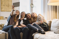 Happy family of four taking selfie through digital tablet at home 11016033584| 写真素材・ストックフォト・画像・イラスト素材|アマナイメージズ