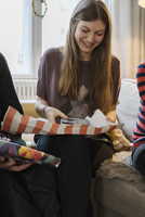 Young woman opening a present at home 11016033595| 写真素材・ストックフォト・画像・イラスト素材|アマナイメージズ