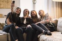 Happy family of four talking selfie through mobile phone at home 11016033596| 写真素材・ストックフォト・画像・イラスト素材|アマナイメージズ