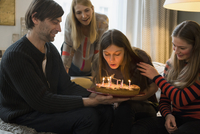 Family looking at young woman blowing out birthday candles at home 11016033605| 写真素材・ストックフォト・画像・イラスト素材|アマナイメージズ