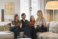 Happy family of four sitting together on sofa at home 11016033607| 写真素材・ストックフォト・画像・イラスト素材|アマナイメージズ