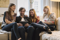 Happy family with father using digital tablet in living room 11016033609| 写真素材・ストックフォト・画像・イラスト素材|アマナイメージズ