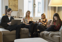 Parents and daughters using laptop and mobile devices on sofa in living room 11016033611| 写真素材・ストックフォト・画像・イラスト素材|アマナイメージズ