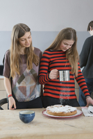 Young woman watching sister sprinkling tart with icing sugar at home 11016033615| 写真素材・ストックフォト・画像・イラスト素材|アマナイメージズ