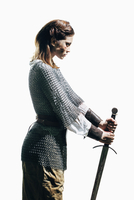 Side view of woman wearing chain mail with sword standing against white background 11016033640| 写真素材・ストックフォト・画像・イラスト素材|アマナイメージズ