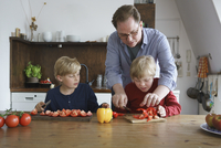 Father assisting disabled son to chop vegetables with boy at table in kitchen 11016033773| 写真素材・ストックフォト・画像・イラスト素材|アマナイメージズ