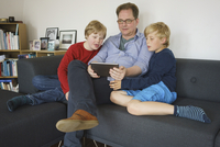 Father and sons sitting on sofa while using digital tablet at home 11016033776| 写真素材・ストックフォト・画像・イラスト素材|アマナイメージズ