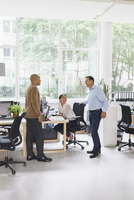 Happy businessmen communicating with female colleague at creative office 11016034249| 写真素材・ストックフォト・画像・イラスト素材|アマナイメージズ