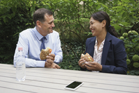 Happy business colleagues having snack at table against plants 11016034261| 写真素材・ストックフォト・画像・イラスト素材|アマナイメージズ