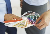 Midsection of businessmen choosing color swatches at creative office 11016034302| 写真素材・ストックフォト・画像・イラスト素材|アマナイメージズ