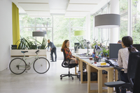 Business people working in brightly lit creative office 11016034304| 写真素材・ストックフォト・画像・イラスト素材|アマナイメージズ