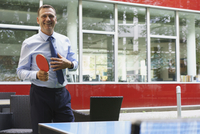Smiling business person playing table tennis at creative office 11016034314| 写真素材・ストックフォト・画像・イラスト素材|アマナイメージズ