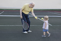 Girl giving tennis ball to grandfather while standing at playing field 11016034590| 写真素材・ストックフォト・画像・イラスト素材|アマナイメージズ
