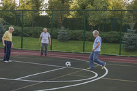 Senior friends playing soccer by fence at field 11016034595| 写真素材・ストックフォト・画像・イラスト素材|アマナイメージズ