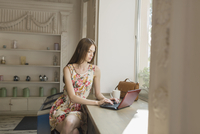 Young woman using laptop while sitting by window at cafe 11016034641| 写真素材・ストックフォト・画像・イラスト素材|アマナイメージズ