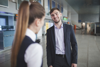 Young businessman smiling while looking at businesswoman at airport 11016034801| 写真素材・ストックフォト・画像・イラスト素材|アマナイメージズ