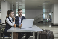 Young business couple using laptop at table in airport 11016034808| 写真素材・ストックフォト・画像・イラスト素材|アマナイメージズ