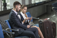 Young business couple using mobile phones while waiting at airport 11016034811| 写真素材・ストックフォト・画像・イラスト素材|アマナイメージズ
