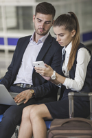 Young business couple using smart phone while waiting at airport 11016034814| 写真素材・ストックフォト・画像・イラスト素材|アマナイメージズ