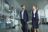 Young business people looking at each other while walking in airport 11016034817| 写真素材・ストックフォト・画像・イラスト素材|アマナイメージズ
