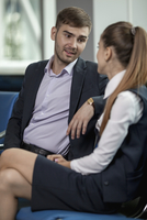 Young businessman talking with female colleague at airport 11016034818| 写真素材・ストックフォト・画像・イラスト素材|アマナイメージズ