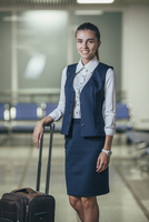 Portrait of smiling young businesswoman with luggage at airport 11016034820| 写真素材・ストックフォト・画像・イラスト素材|アマナイメージズ