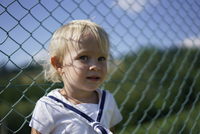 Cute toddler standing against chainlink fence 11016035407| 写真素材・ストックフォト・画像・イラスト素材|アマナイメージズ