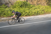 Side view of man cycling on country road 11016035457| 写真素材・ストックフォト・画像・イラスト素材|アマナイメージズ