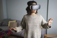 Woman using virtual reality headset while standing in living room 11016035586| 写真素材・ストックフォト・画像・イラスト素材|アマナイメージズ