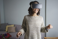 Happy woman using virtual reality headset while standing in living room 11016035606| 写真素材・ストックフォト・画像・イラスト素材|アマナイメージズ